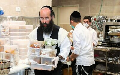 Volunteers from the Ezrat Achim organization in Beit Shemesh prepare food for distribution to Israelis who are homebound due to the COVID-19 pandemic. (Courtesy)