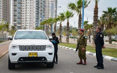 An IDF officer helps police run a checkpoint during the coronavirus outbreak on April 2, 2020. (Israel Defense Forces)