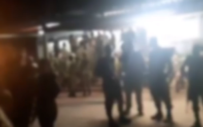 Blurry footage aired on Channel 12 on April 3, 2020, shows a large gathering of soldiers outside a mess hall at a base in central Israel (video screenshot)