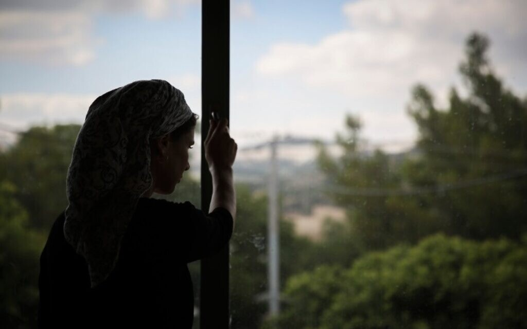 An Orthodox Jewish woman looks out the window of the abused women's shelter in Beit Shemesh, July 15, 2014. (Hadas Parush/Flash90)