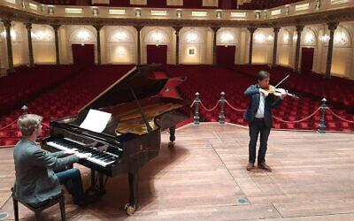 Pianist Marc Wielart and violinist Eduardo Paredes Crespo playing Israel's national anthem at the Concergebouw hall in Amsterdam, the Netherlands in April 2020. (Courtesy of Barry Mehler via JTA)