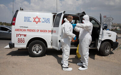 Magen David Adom workers wearing protective clothing disinfect their ambulance after taking care of a patient with a possible coronavirus infection on April 14, 2020 (Nati Shohat/Flash90)