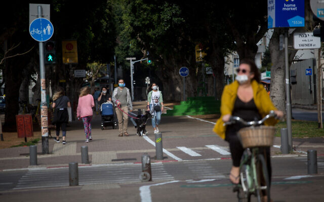 People wear protective masks in Tel Aviv, on April 18, 2020 (Miriam Alster/FLASH90)