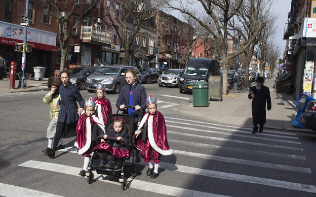 A Hasidic family, dressed up for the jewish holiday purim, crosses the street on March 10, 2020 in the Williamsburg neighborhood  Brooklyn, New York. (Andrew Lichtenstein/Corbis via Getty Images via JTA)