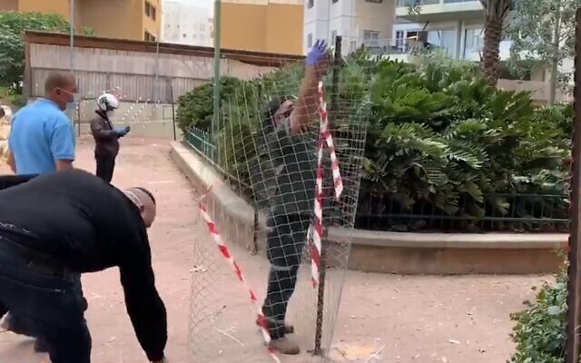 Ramat Gan municipal workers put up a fence to block pedestrians from neighboring Bnei Brak, April 6, 2020 (Screen grab/Ynet)
