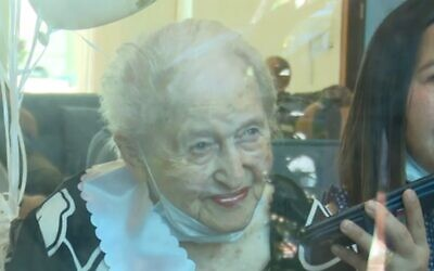 Sara Treves celebrates her 107th birthday through the glass window of her nursing home (Screen grab/Channel 12)