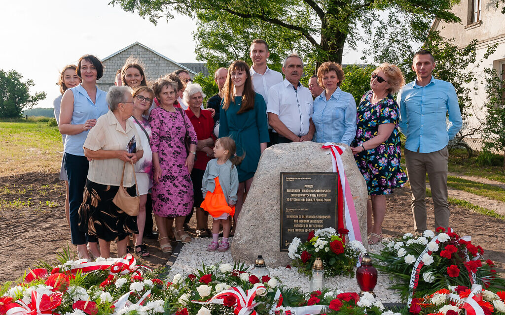 A Polish family at a memorial honoring their relatives who tried to rescue Jews during World War II. (Courtesy Pilecki Institute)