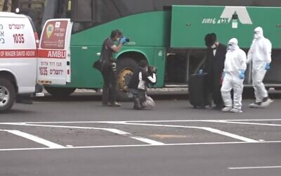 An Israeli man suspected of knowingly taking a bus to Jerusalem after testing positive for the coronavirus is escorted by Magen David Adom medical workers from the bus to an ambulance on April 5, 2020 (Channel 12 screenshot)