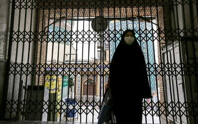 A woman walks past the closed gate outside the Imamzadeh Saleh in the Iranian capital Tehran's Shemiran district on April 25, 2020, during the Muslim holy month of Ramadan, as all mosques and places of worship are closed due to the COVID-19 coronavirus pandemic. (ATTA KENARE / AFP)