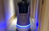 This photo taken on April 28, 2020, shows a robot capable of taking elevators and navigating hallways on its own delivering food to a guest at a quarantine hotel housing people from Hubei province in Beijing (Jing Xuan TENG / AFP)