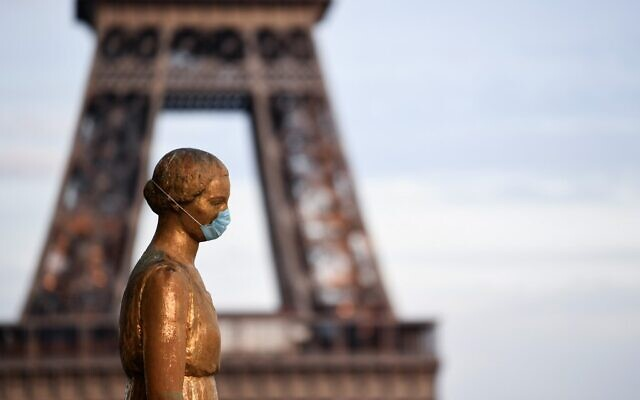 A picture taken on May 2, 2020, shows a bronze statue wearing a face mask at the Parvis des Droits de l'Homme, with the Eiffel Tower in background in Paris, on the 47th day of a strict lockdown in France aimed at curbing the spread of the COVID-19 pandemic, caused by the novel coronavirus. (Alain JOCARD / AFP)