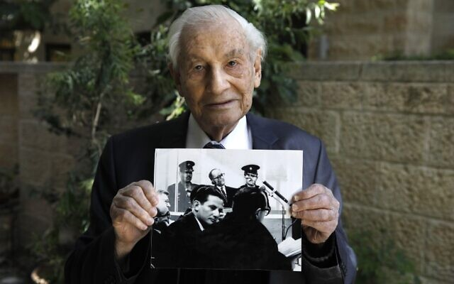 Gabriel Bach, 93, a former judge of the Supreme Court of Israel and a former deputy prosecutor during the trial of Adolf Eichmann, poses for a picture while holding a photograph showing him (below) during Eichmann's (top) trial, at the yard of his home in Jerusalem on May 3, 2020.(Photo by MENAHEM KAHANA / AFP)