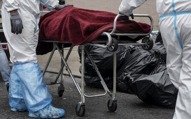 Medical workers in hazmat suits transport a body on a stretcher outside a funeral home in the New York City borough of Brooklyn on April 30, 2020. (Johannes Eisele/AFP)
