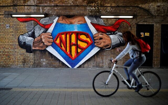 A cyclist passes artwork celebrating the National Health Service (NHS) in central London, May 5, 2020, during the nationwide lockdown due to the novel coronavirus COVID-19 outbreak. (Tolga Akmen/AFP)