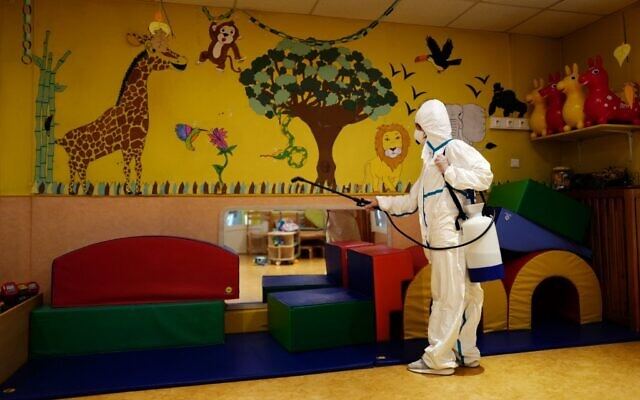 A member of a desinfection squad cleans a nursery in the French Riviera city of Cannes, southern France, on May 6, 2020, as the nurseries in France are to gradually reopen from May 11, when a partial lifting of restrictions due to the Covid-19 pandemic caused by the novel coronavirus comes into effect. (Valery Hache/AFP)