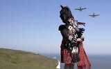 Pipe major Andy Reid of The Scots Guards plays his pipes on the cliffs of Dover, southern England on May 6, 2020 as two Spitfires from the battle of Britain memorial flight fly over him during a posed picture to commemorate the 75th anniversary of VE day (Richard Pohle / POOL / AFP)