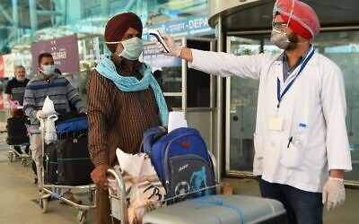 A health worker checks the body temperature of a British national queueing before checking-in for a special flight to London during a government-imposed nationwide lockdown as a preventive measure against the spread of the COVID-19 coronavirus, at the Sri Guru Ram Dass jee International Airport on the outskirts of Amritsar on May 7, 2020. (NARINDER NANU / AFP)