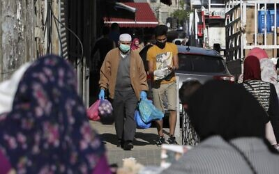 Palestinians shop while wearing protective masks amid the ongoing coronavirus pandemic in the West Bank city of Ramallah, on May 7, 2020. (Abbas Momani/AFP)