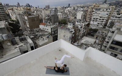 In this file photo taken on April 27, 2020 Lebanese Yoga instructor Rabih el-Medawar, 29, practices Acroyoga with his Ukranian wife, fellow Yoga instructor and professional choreographer, Alona Aleksandrova, 24, on the roof of their apartment building in Beirut's Ain El-Remmaneh district on April 27, 2020 during the coronavirus (COVID-19) pandemic. (Photo by JOSEPH EID / AFP)