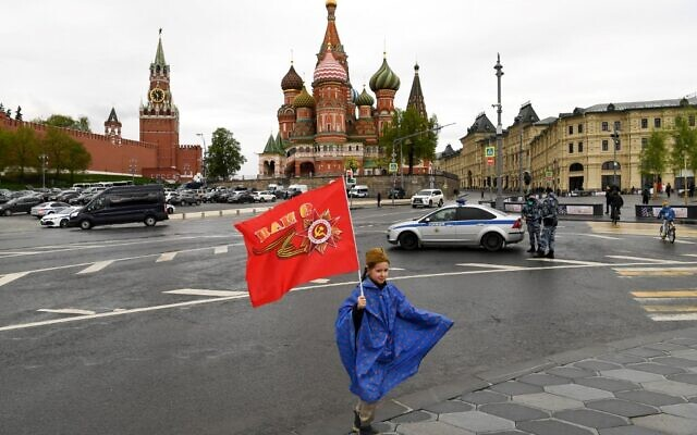 A girl with a red flag poses for a photo in downtown Moscow as she marks the 75th anniversary of the victory over Nazi Germany in World War II, May 9, 2020. (Kirill KUDRYAVTSEV / AFP)