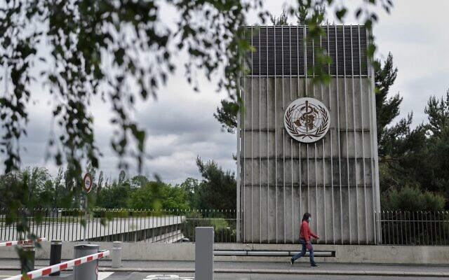 A woman wearing a protective facemask walks underneath a sign at the World Health Organization (WHO) headquarters in Geneva, Switzerland, May 12, 2020. (Fabrice Coffrini/AFP)