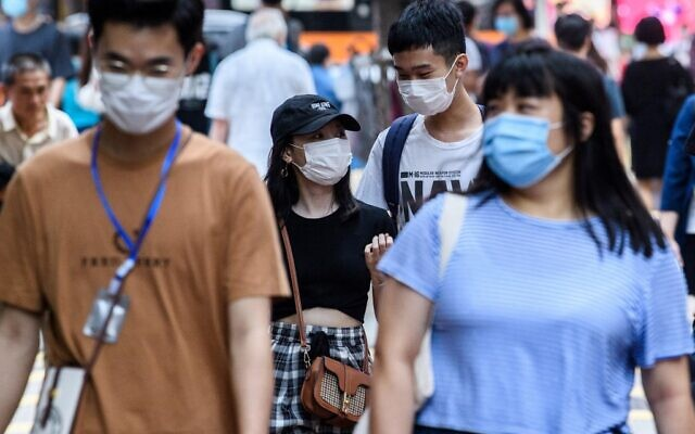 Pedestrians wear face masks as a precautionary measure against the coronavirus as they walk on a street in Hong Kong on May 13, 2020. (Anthony WALLACE / AFP)