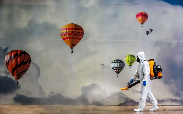 An employee wearing protective gear disinfects a shopping mall as a preventive measure against the COVID-19 coronavirus in Caxias do Sul, Brazil on May 13, 2020. (SILVIO AVILA / AFP)