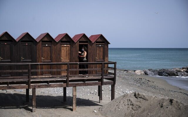 The owner of a bathing facility prepares beach cabins for the upcoming summer season, on May 14 2020 in Albissola Marina, near Savona, Liguria (MARCO BERTORELLO / AFP)