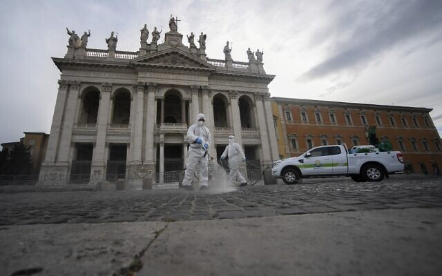 Employees of a disinfecting services company, wearing protective overalls and mask, sprays sanitizer on the forecourt during the sanitation of the Archbasilica of Saint John Lateran (San Giovanni in Laterano) in Rome on May 15, 2020 (Filippo MONTEFORTE / AFP)
