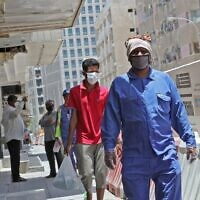 Workers wearing protective masks walk by on a street in Qatar's capital Doha, on May 17, 2020, as the country begins enforcing the world's toughest penalties for failing to wear masks in public, as it battles one of the world's highest coronavirus infection rates. (Photo by KARIM JAAFAR / AFP)