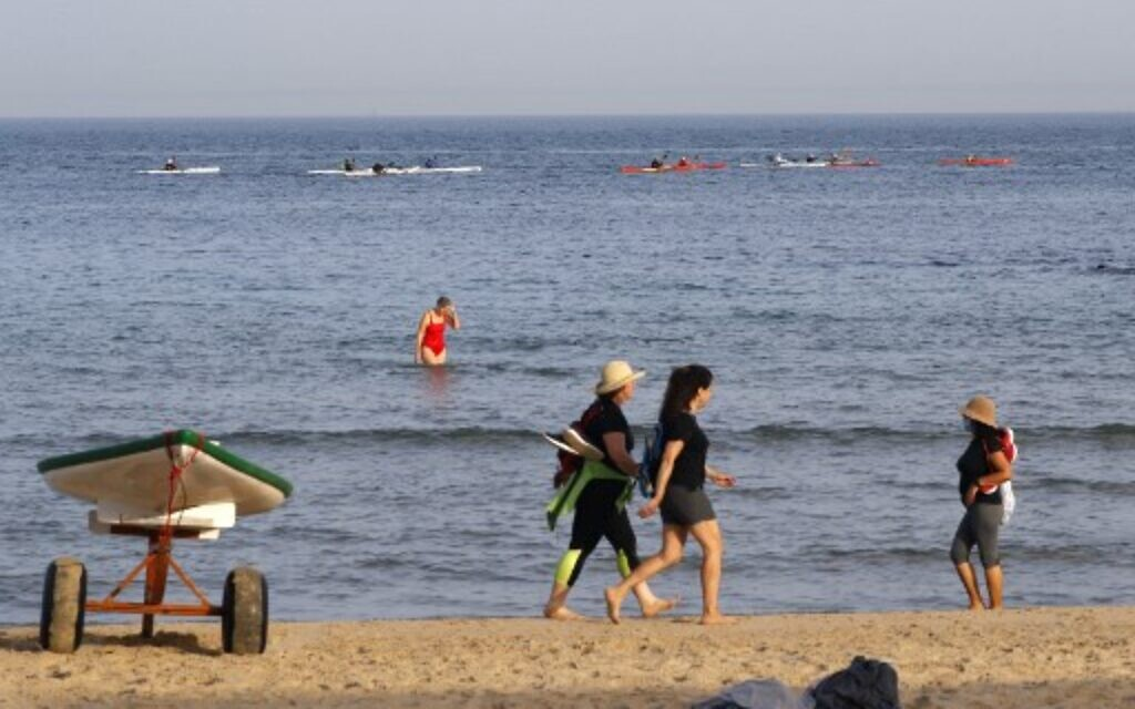 Beach-goers walk at a beach in the coastal city of Tel Aviv on May 20, 2020, as beaches open for the first time after two months of confinement due to the COVID-19 coronavirus pandemic. (Jack Guez/AFP)