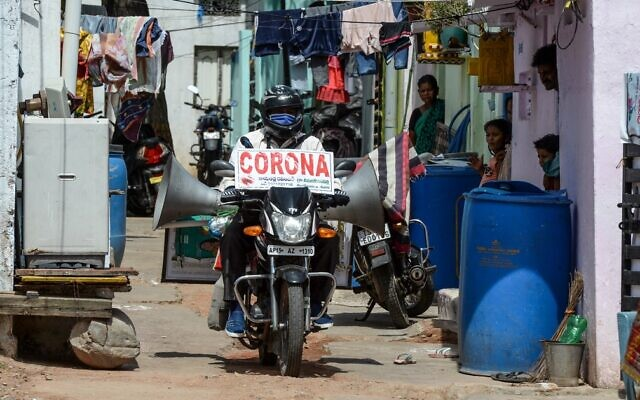 Farmer Bamandla Ravinder, who drives around on his bike in the villages of Telangana state to spread awareness about the coronavirus, rides through the slums in Hyderabad on May 21, 2020. (Noah Seelam/AFP)