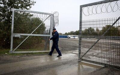 Illustrative: A Hungarian policeman closes a razor wire fence at a migrant transit center near Roszke, at the border crossing with Serbia, October 29, 2019. (Oliver Bunic/AFP)