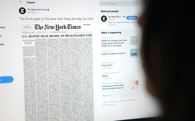 This picture from May 23, 2020, shows a woman looking at a computer screen with a tweet by the New York Times account showing the early edition front page of the newspaper for May 24, 2020 (Agustin Paullier/AFP)