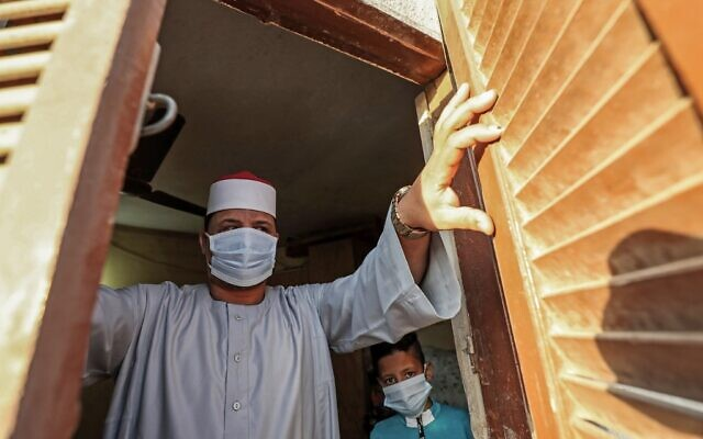The Imam of a local mosque in the village of Shamma in Egypt's northern Nile delta province of Menoufia stands clad in mask due to the COVID-19 coronavirus pandemic by a window near the mosque early on May 24, 2020, before the prayers of Eid al-Fitr, the Muslim holiday which starts at the conclusion of the holy fasting month of Ramadan (Mohamed el-Shahed / AFP)