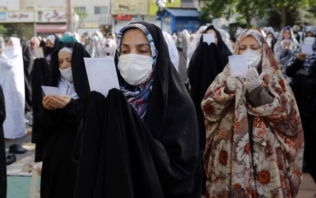 Muslim women worshipers, standing spaced from each other with some clad in masks as a measure against the COVID-19 coronavirus pandemic, as they gather to attend the prayers of Eid al-Fitr, the Muslim holiday which starts at the conclusion of the holy fasting month of Ramadan, in Iran's capital Tehran on May 24, 2020 (STRINGER / AFP)