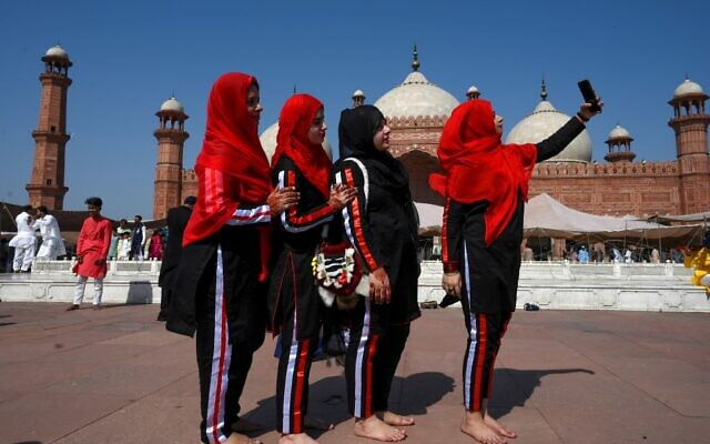 Muslim women take selfies after offering Eid al-Fitr prayers at the Badshahi Mosque in Lahore on May 24, 2020 (Arif ALI / AFP)