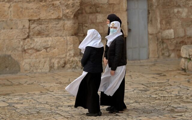 Three Catholic nuns wearing face masks stand in front of the Church of the Holy Sepulchre in Jerusalem's Old City as they await its reopening opening in Jerusalem, May 24, 2020. (Emmanuel Dunand/AFP)