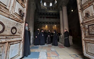 Greek Orthodox, Coptic Orthodox, Armenian, and Franciscan clergymen stand inside the Church of the Holy Sepulchre in Jerusalem's Old City on May 24, 2020, (GALI TIBBON/AFP)
