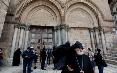 Disappointed visitors and worshipers gather in front of the shut doors of the Church of the Holy Sepulchre in Jerusalem's Old City on May 24, 2020, closed due to the COVID-19 pandemic lockdown. (GALI TIBBON / AFP)