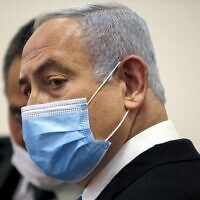 Prime Minister Benjamin Netanyahu, wearing a protective face mask, in the courtroom at the District Court of Jerusalem on May 24, 2020, at the start of his corruption trial. (Ronen Zvulun / POOL / AFP)
