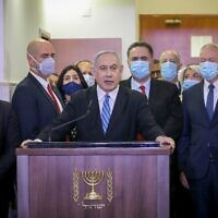 Prime Minister Benjamin Netanyahu delivers a statement before entering a courtroom at the Jerusalem District Court on May 24, 2020, for the start of his corruption trial. Among those alongside him from left are Likud MKs and ministers Gadi Yevarkan, Amir Ohana, Miri Regev, Nir Barkat, Israel Katz, Tzachi Hanegbi, Yoav Gallant and David Amsalem (Yonathan SINDEL / POOL / AFP)
