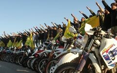 Supporters of the Lebanese terror group Hezbollah salute as they stand behind motorcycles carrying the Shiite movement's flags in the southern Lebanese district of Marjayoun on the border with Israel, May 25, 2020. (Mahmoud Zayyat/AFP)