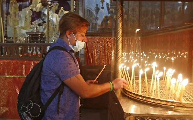 A Christian worshiper lights candles in Bethlehem's Church of the Nativity following its reopening as Palestinian authorities eased coronavirus restrictions in the West Bank, on May 26, 2020. (Musa Al SHAER / AFP)