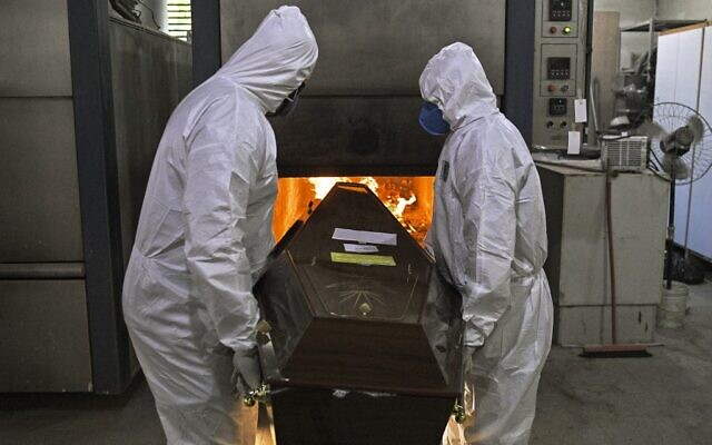 Crematorium workers wearing personal protective equipment as a preventive measure against the spread of the coronavirus pandemic, push a corpse into the oven of its crematorium at Sao Francisco Xavier cemetery, in Rio de Janeiro, Brazil on May 29, 2020 (CARL DE SOUZA / AFP)