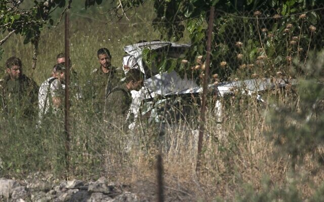 Israeli soldiers inspect a car at the scene of an apparent attempted car-ramming attack near the West Bank settlement of Halamish on May 29, 2020. (Abbas Momani/AFP)