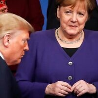 In this file photo taken on December 04, 2019 Germany's Chancellor Angela Merkel (R) looks at US President Donald Trump walking past her during a group photo as part of the NATO summit at the Grove hotel in Watford, northeast of London (CHRISTIAN HARTMANN / POOL / AFP)