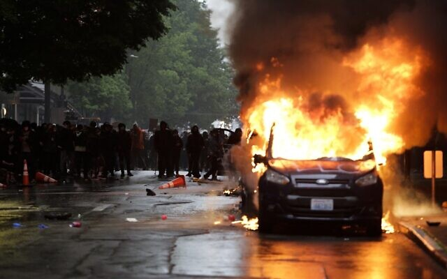 Vehicles burn following demonstrations protesting the death of George Floyd, a black man who died May 25 in the custody of Minneapolis Police, in Seattle, Washington on May 30, 2020 (Jason Redmond / AFP)
