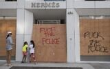 A family looks at a looted Hermes store on the iconic Rodeo Drive after demonstrators protested the death of George Floyd in Beverly Hills, California on May 31, 2020. (Mark RALSTON / AFP)