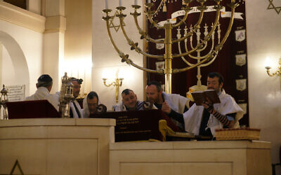 Rabbi Michael Azoulay, second from right, reading the Torah with congregants at the synagogue of Neuilly-sur-Seine, a Paris suburb, Dec. 11, 2017. (Cnaan Liphshiz/JTA)